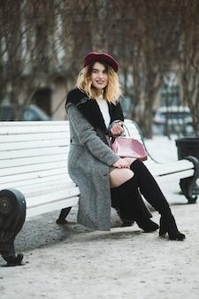 Vertikaler schuss des flachen fokus einer attraktiven frau in der winterkleidung, die auf einer weißen bank sitzt