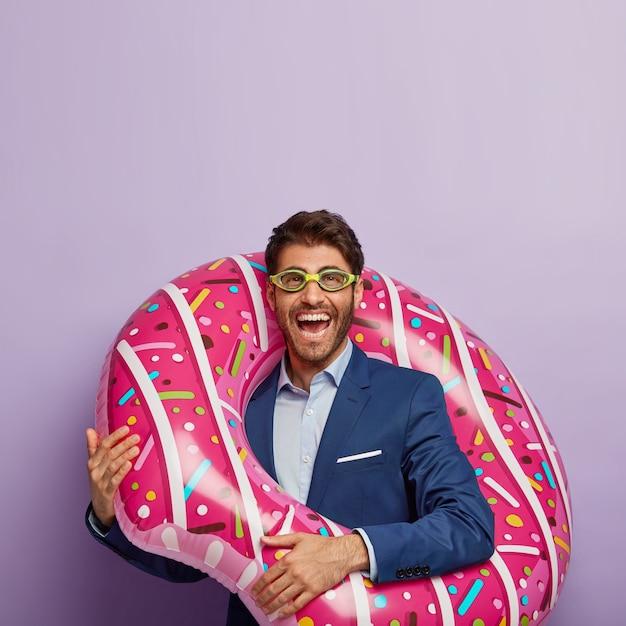 Vertikaler schuss des fröhlichen jungen mannes mit borsten, trägt schutzbrille und elegante kleidung