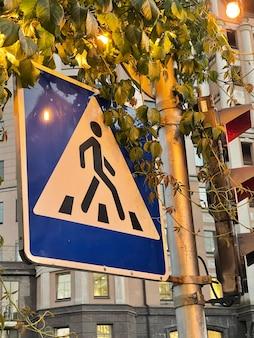 Vertikaler schuss des fußgängerüberwegzeichens in den blättern
