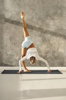 Vertikaler schuss des gebräunten athletischen jungen mannes, der im fitnessstudio arbeitet, das variation der stehenden teilung oder urdhva prasarita eka padasana gegen graue wand tut. fit sportlichen kerl, der fortgeschrittenes yoga drinnen praktiziert