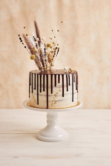 Vertikaler schuss des köstlichen boho-kuchens mit schokoladentropfen und blumen oben mit goldenen verzierungen