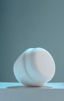 Vertikaler schuss des legens des lotionscremebehälters auf weißer plattform mit kopienraum