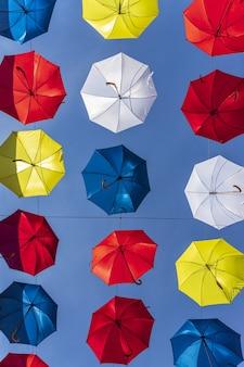 Vertikaler schuss des niedrigen winkels von bunten regenschirmen in der straße von sancerre, frankreich