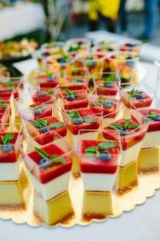 Vertikaler schuss des puddings mit früchten in den bechern