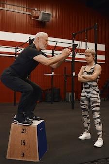 Vertikaler schuss des schönen selbstbewussten fitnesslehrers der frau, der arme auf ihrer brust kreuzt und ihren älteren mann beobachtet, der kniebeugen tut, muskeln während des persönlichen trainings im modernen fitnessstudio aufbauend