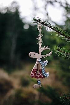 Vertikaler schuss des spielzeughirsches hing am weihnachtsbaum