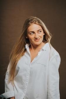 Vertikaler schuss einer attraktiven kaukasischen blonden frau in einem weißen hemd, das auf einer braunen wand aufwirft