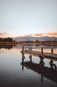 Vertikaler schuss einer frau, die auf dem pier sitzt, der die gitarre in cromwell, neuseeland spielt