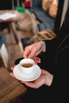 Vertikaler schuss einer frau, die eine tasse espresso hält
