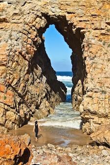 Vertikaler schuss einer frau, die vor einer höhle steht, die zum ozean führt