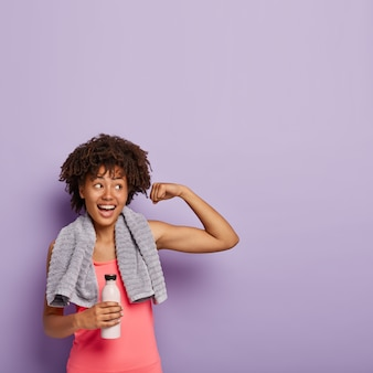 Vertikaler schuss einer fröhlichen dunkelhäutigen frau hebt den muskulösen arm, hat fitness-training, trinkt wasser aus der flasche