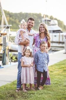 Vertikaler schuss einer glücklichen familie, die auf dem gras nahe dem hafen steht