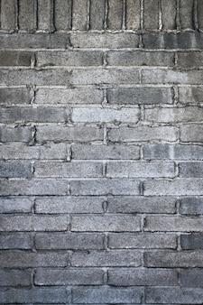 Vertikaler schuss einer grauen gemauerten wand mit zement