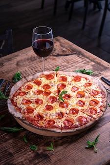 Vertikaler schuss einer köstlichen käsigen peperoni-pizza mit einem glas wein auf einem holztisch