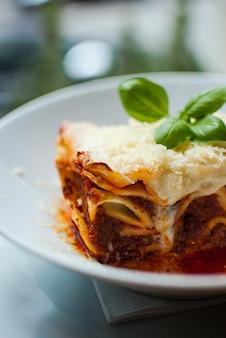 Vertikaler schuss einer köstlichen lasagne auf einem weißen teller