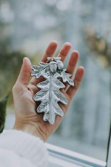 Vertikaler schuss einer person, die eine christbaumverzierung hält