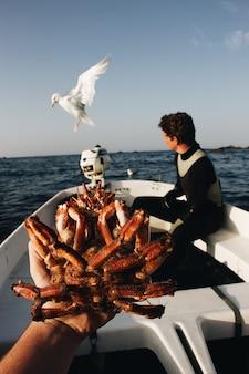 Vertikaler schuss einer person, die eine krabbe mit einem verschwommenen mann hält, der auf dem boot nahe einer möwe sitzt