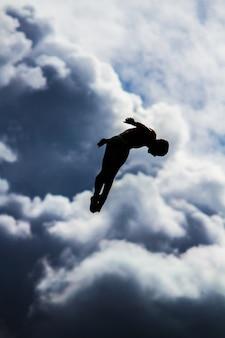 Vertikaler schuss einer person, die in die luft mit einem unscharfen himmel springt