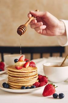 Vertikaler schuss einer person, die sirup auf die veganen pfannkuchen mit früchten setzt