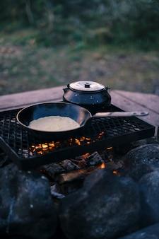 Vertikaler schuss einer pfanne und eines kessels auf dem grill