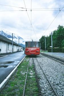Vertikaler schuss einer roten straßenbahn, die sich durch die schienen vorwärts bewegt