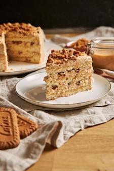 Vertikaler schuss einer scheibe des köstlichen lotusplätzchenkuchens mit karamell mit keksen auf dem tisch