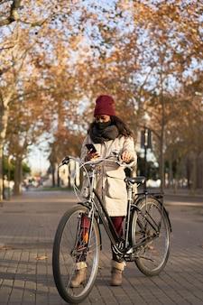 Vertikaler schuss einer schwarzen frau in der winterkleidung, die mit einem fahrrad steht, das am telefon in einer stadt bei sonnenuntergang spricht. Premium Fotos