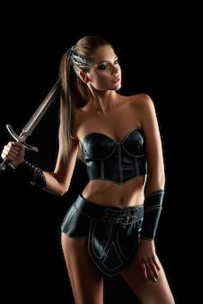 Vertikaler schuss einer sexy jungen amazonas-frau, die mit einem schwert auf schwarzer wand verführt sexualität schönheit gepanzerte waffe furchtlose mutige stammeskultur traditioneller kriegerkämpfer.