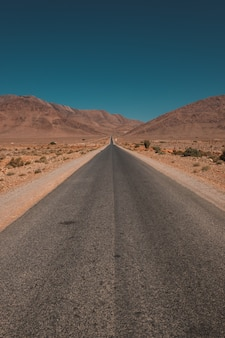 Vertikaler schuss einer straße in der mitte der wüste und der berge, die in marokko gefangen genommen werden
