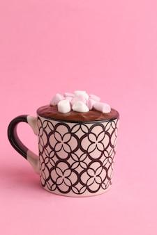 Vertikaler schuss einer tasse heißer schokolade mit marshmallows lokalisiert auf einem rosa hintergrund