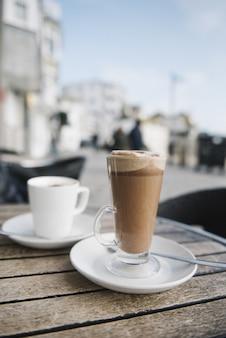 Vertikaler schuss einer tasse kalten kaffees auf dem tisch