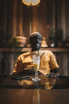 Vertikaler schuss einer tasse smoothie auf einem tisch vor einem afroamerikaner-mann Kostenlose Fotos