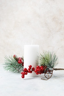Vertikaler schuss einer weißen kerze, die von weihnachtshöhlen und -blättern auf einer weißen marmoroberfläche umgeben ist