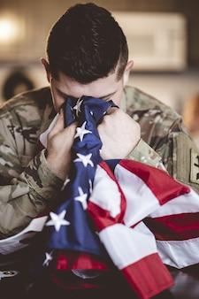 Vertikaler schuss eines amerikanischen soldaten, der mit der amerikanischen flagge in seinen händen trauert und betet