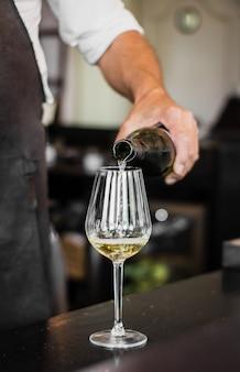 Vertikaler schuss eines barkeepers, der einen wein in ein glas gießt