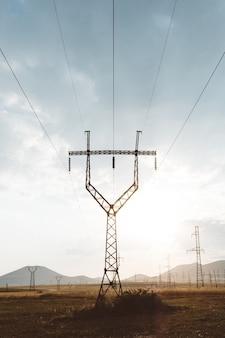 Vertikaler schuss eines elektrischen pfostens mit metallgeländern oben unter einem bewölkten himmel