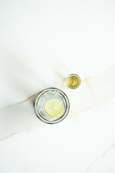 Vertikaler schuss eines glases limonade auf einer weißen oberfläche