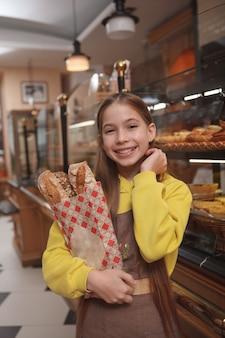 Vertikaler schuss eines glücklichen niedlichen jungen bäckermädchens, das schürze trägt und eltern in ihrem familiencafé hilft