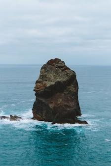 Vertikaler schuss eines großen steins in der mitte des ozeans, der in madeira, portugal gefangen genommen wird