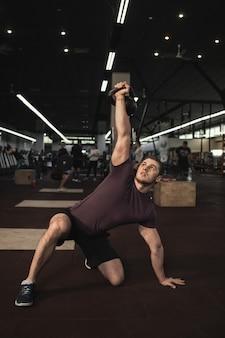 Vertikaler schuss eines gutaussehenden muskulösen männlichen athleten, der kettlebell-türkisch tut, steht auf