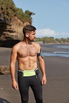 Vertikaler schuss eines halbnackten gesunden männlichen athleten macht pause nach dem training