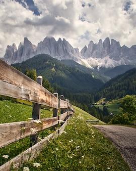 Vertikaler schuss eines hölzernen zauns mit hohen felsigen klippen in funes valley, st. italien