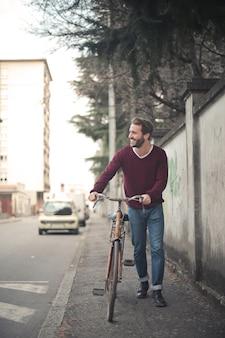 Vertikaler schuss eines jungen mannes, der ein fahrrad auf bürgersteig reitet