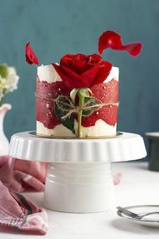 Vertikaler schuss eines kleinen ausgefallenen kuchens mit einer roten rose auf einem weißen tablett