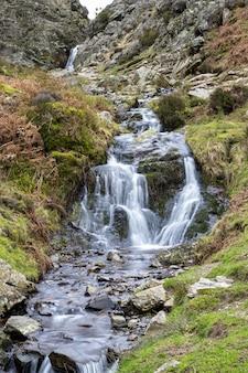 Vertikaler schuss eines kleinen wasserfalls, der von einem steilen berg fließt