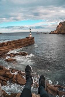 Vertikaler schuss eines leuchtfeuers an einem steinernen pier in pasajes san pedro, gipuzkoa, spanien