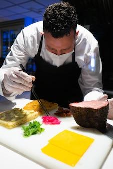 Vertikaler schuss eines männlichen kochs, der eine gesichtsmaske trägt, die eine köstliche mahlzeit vorbereitet