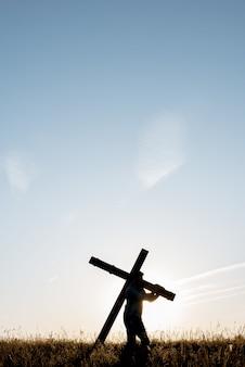 Vertikaler schuss eines mannes, der ein handgemachtes holzkreuz in einem grasfeld unter einem blauen himmel trägt