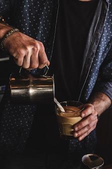 Vertikaler schuss eines mannes, der milch in ein glas kaffee gießt
