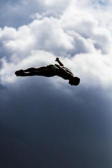 Vertikaler schuss eines mannes, der mit einem verschwommenen himmel in die luft springt